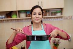 准备一个盘的少妇在她的厨房里 库存照片