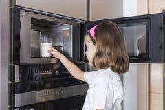 准备一杯牛奶的孩子 免版税库存照片