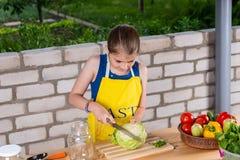 准备一棵新鲜的圆白菜的女孩 库存照片