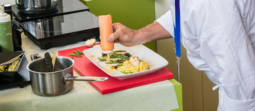 准备一顿可口膳食的一位专业厨师的手 库存图片