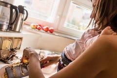 准备一顿膳食的年轻母亲在厨房里 免版税库存图片