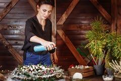 准备与人为雪的年轻逗人喜爱的微笑的妇女设计师圣诞节常青树花圈 制造商  免版税图库摄影