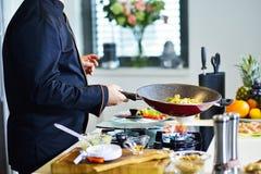 准备与各种各样的菜和肉的成熟厨师一顿膳食 免版税库存图片