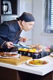 准备与各种各样的菜和肉的成熟厨师一顿膳食 免版税库存照片