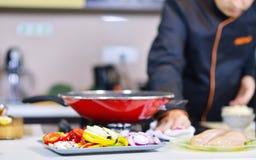 准备与各种各样的菜和肉的成熟厨师一顿膳食 免版税图库摄影