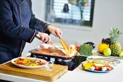 准备与各种各样的菜和肉的成熟厨师一顿膳食 图库摄影