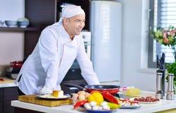 准备与各种各样的菜和肉的成熟厨师一顿膳食 库存照片