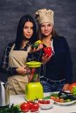 准备与搅拌器的两名妇女素食主义者蔬菜汁 库存照片