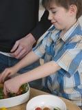准备与父亲的男孩沙拉在厨台 免版税库存照片