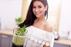 准备健康圆滑的人的适合的微笑的少妇在现代厨房里 库存照片