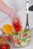 准备健康沙拉的妇女在她的现代厨房里 库存照片
