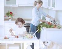 (8-9)准备健康膳食的母亲和女儿在厨房里 免版税库存图片