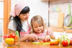 准备健康食物的妇女和孩子女孩 免版税库存照片