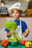 准备健康食物的小微笑的厨师男孩在 免版税库存图片
