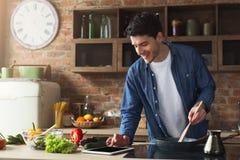 准备健康食物的愉快的人在家庭厨房里 免版税图库摄影