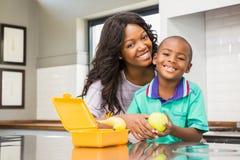 准备儿子学校午餐的微笑的母亲 免版税库存照片