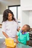 准备儿子学校午餐的微笑的母亲 免版税图库摄影