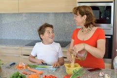 准备午餐和微笑的母亲和儿子 儿子切大蒜 免版税库存照片