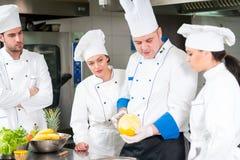 准备可口膳食的一个小组厨师在高豪华餐馆 免版税图库摄影