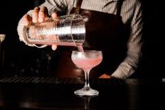准备和倾吐世界性酒精桃红色鸡尾酒的男服务员在酒吧 免版税库存照片
