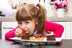 准备和吃蛋糕用果子的小女孩 图库摄影