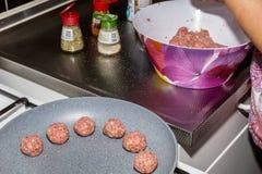 准备和烹调在一个平底锅的丸子在火炉 免版税库存图片
