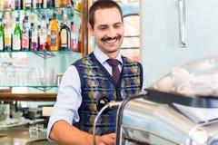 准备咖啡或浓咖啡在咖啡馆酒吧的Barista 库存照片