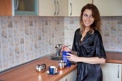 准备咖啡的一个年轻妻子的图片在厨房里早晨 免版税库存图片