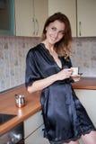 准备咖啡的一个年轻妻子的图片在厨房里早晨 库存照片