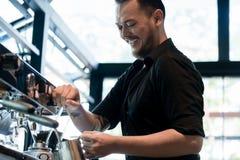 准备咖啡的年轻快乐的barista在一个自动机器 免版税图库摄影
