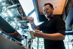 准备咖啡的年轻快乐的barista在一个自动机器 免版税库存照片