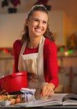 准备圣诞晚餐的愉快的年轻主妇在厨房里 免版税图库摄影