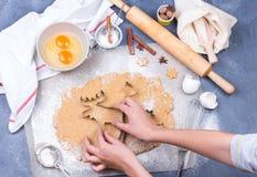 准备圣诞节与切削刀、面团和滚针的姜饼曲奇饼 图库摄影