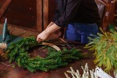 准备圣诞节常青树花圈的年轻逗人喜爱的微笑的妇女设计师 圣诞节装饰制造商与他们的 免版税库存图片