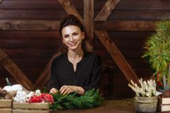 准备圣诞节常青树花圈的年轻逗人喜爱的微笑的妇女设计师 圣诞节装饰制造商与他们的 库存照片