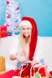 准备圣诞节礼物的圣诞老人帽子的妇女 库存图片