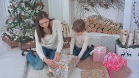 准备圣诞节礼物的小男孩和一个年轻母亲 免版税库存图片