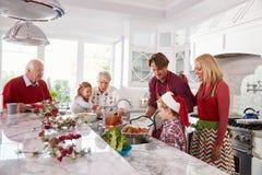 准备圣诞节膳食的大家庭小组在厨房里 库存照片