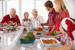 准备圣诞节膳食的大家庭小组在厨房里 免版税库存照片