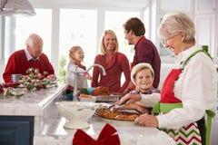 准备圣诞节膳食的大家庭小组在厨房里 免版税图库摄影