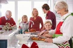 准备圣诞节膳食的大家庭小组在厨房里 免版税库存图片
