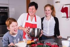 准备圣诞节面包店的母亲和孩子 库存照片