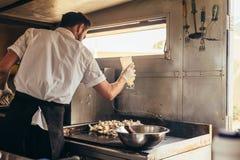 准备在卡车的男性厨师食物 免版税库存图片