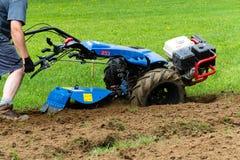 准备在室外庭院的普遍的拖拉机单位土壤 免版税库存照片