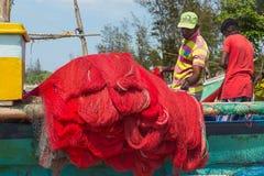 准备在小船的渔夫捕鱼网 免版税库存照片