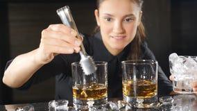 准备在慢动作的女性女服务员侍酒者女服务员酒精鸡尾酒落下的冰块 友好的微笑的服务 股票录像