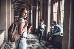 准备在新的学期!拿着书和站立在大学大厅里的确信的妇女看照相机 库存照片