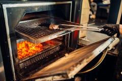 准备在格栅烤箱的厨师一块牛排 免版税库存照片