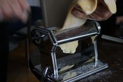 准备在桌上的妇女手工制造意大利烤宽面条面团 库存图片