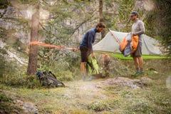 准备垂悬的帐篷的两个人野营在森林森林附近 小组朋友人夏天在山的冒险旅途 图库摄影